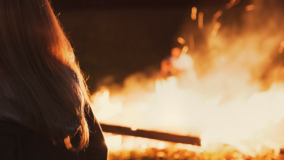 woman standing in front of blazing fire outside